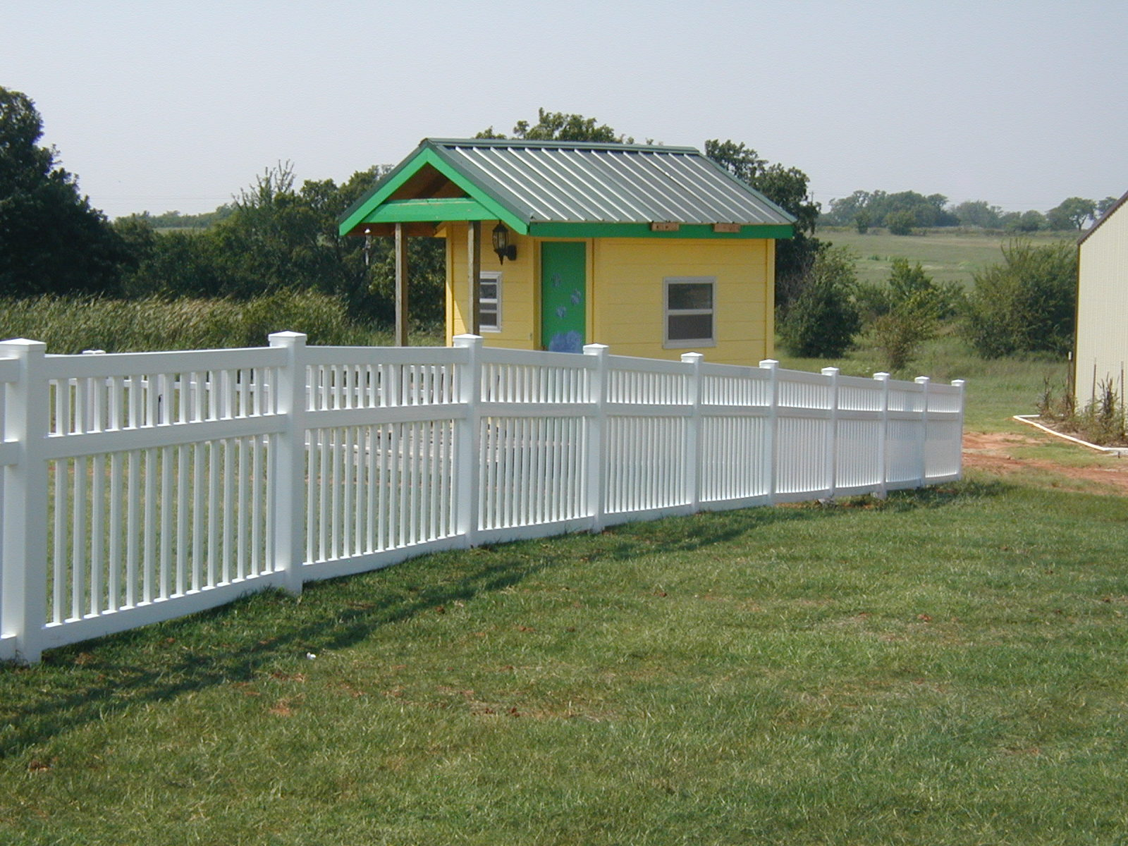 Corner white vinyl picket fence fencing